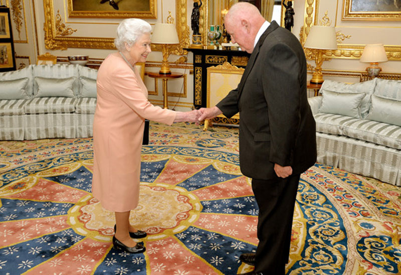 Queen Elizabeth II presenting John Mars with an honorary knighthood in  2017